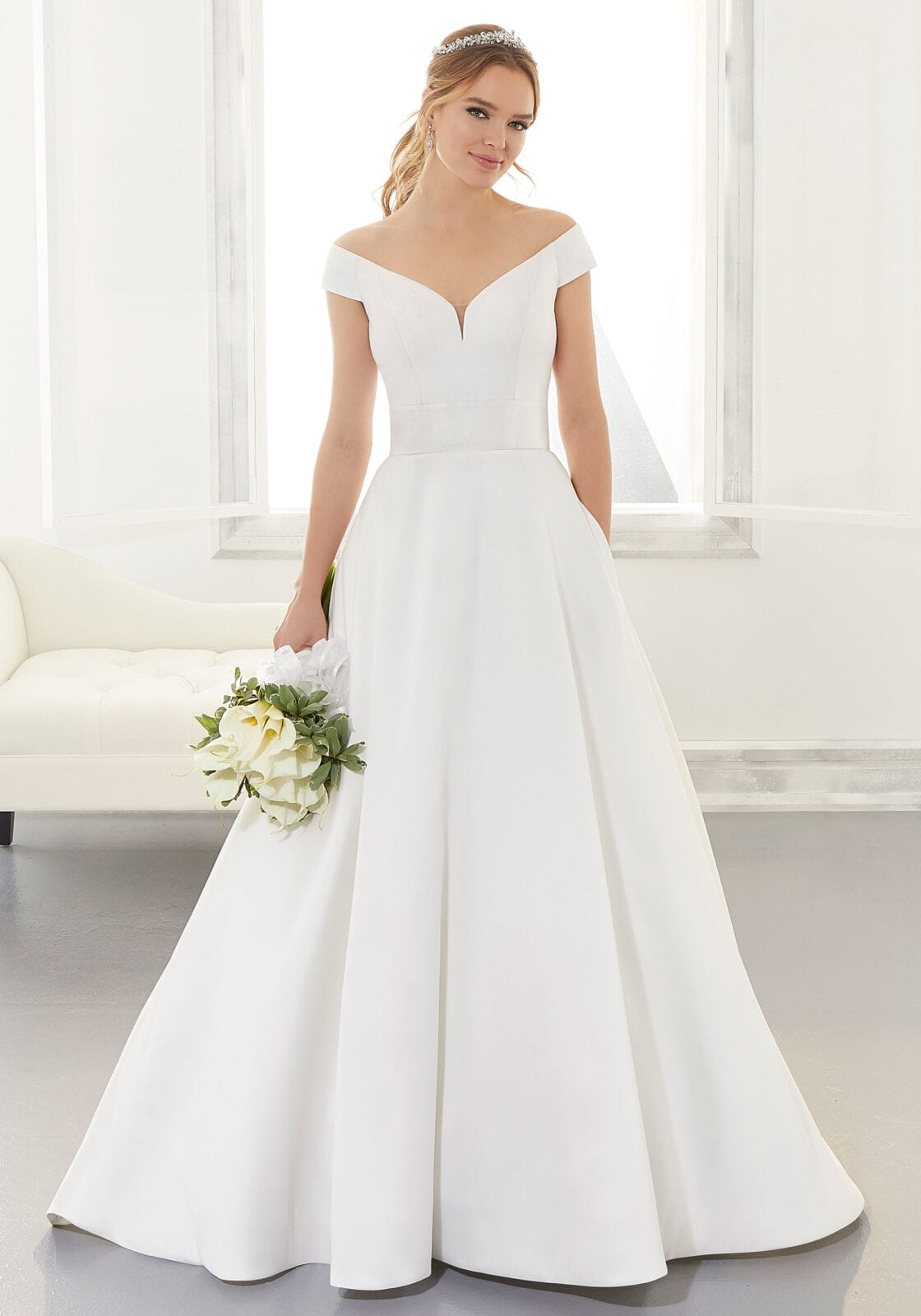 a-line wedding dress in satin has cap sleeves and a off the shoulder neckline.